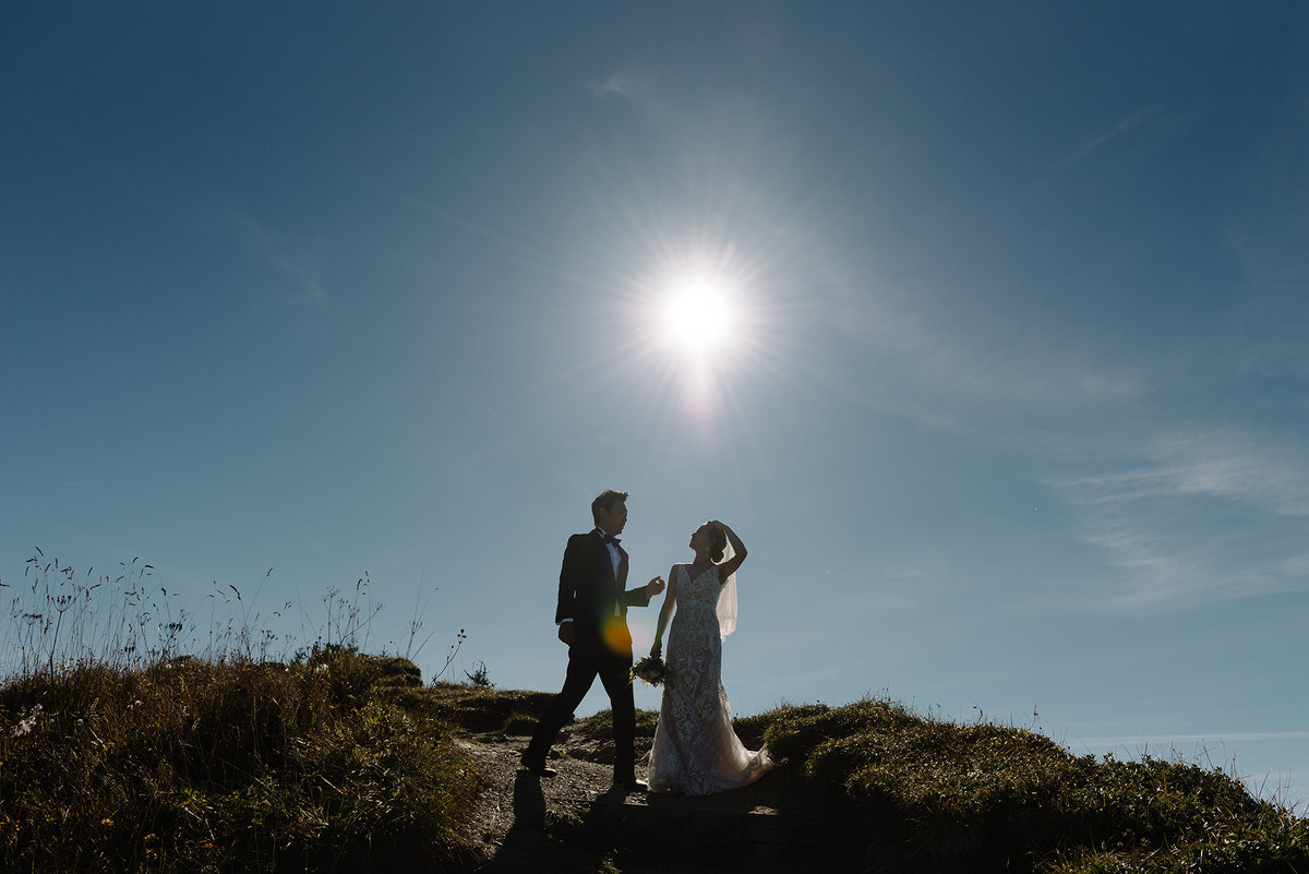 A couple are silhouetted against the sky. She has her hand brushing her hair out of her face and he is reaching out a hand to touch her arm. They are in the mountains and it is late summer.