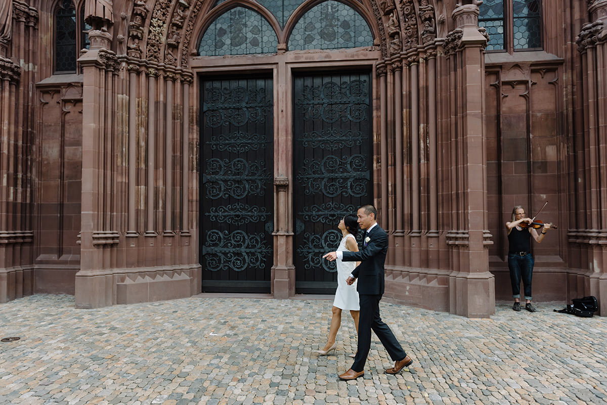 couple walk in front of two huge doors of the Basel Munster, there is a busker behind them, they are on their civil wedding Switzerland