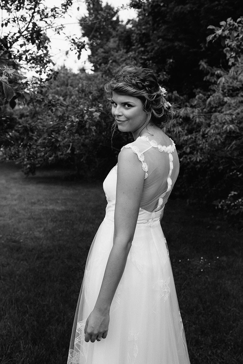 beautiful bride looking at the camera with boho messy hair and daisies on her dress