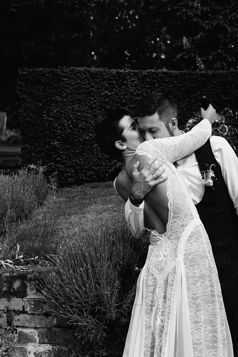groom kisses a brides shoulder. She is wearing a backless dress by Grace Loves Lace Australia Wedding Photography Switzerland