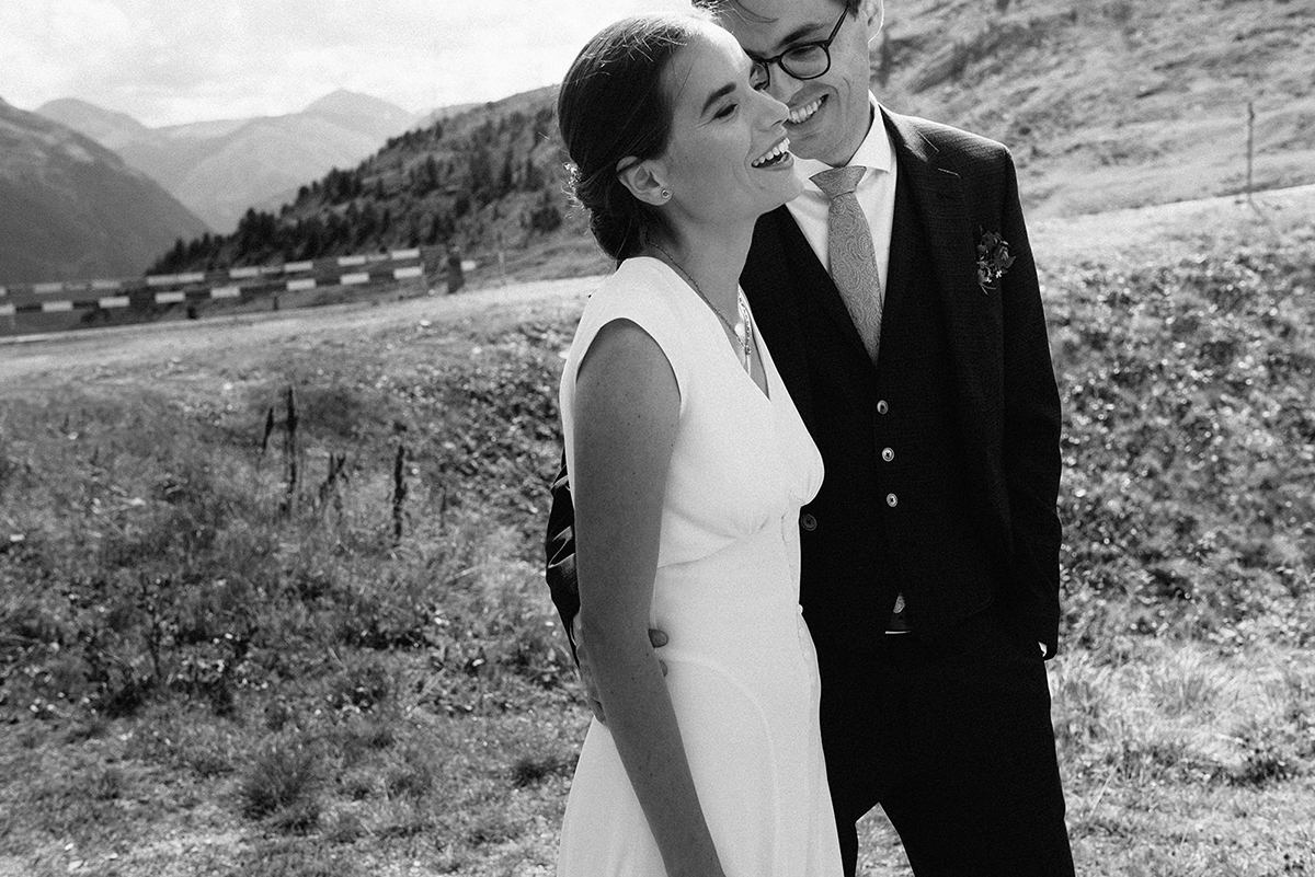 couple hugging in a relaxed way for their wedding photos with a mountain view of Engadin and St Moritz wedding photograohy