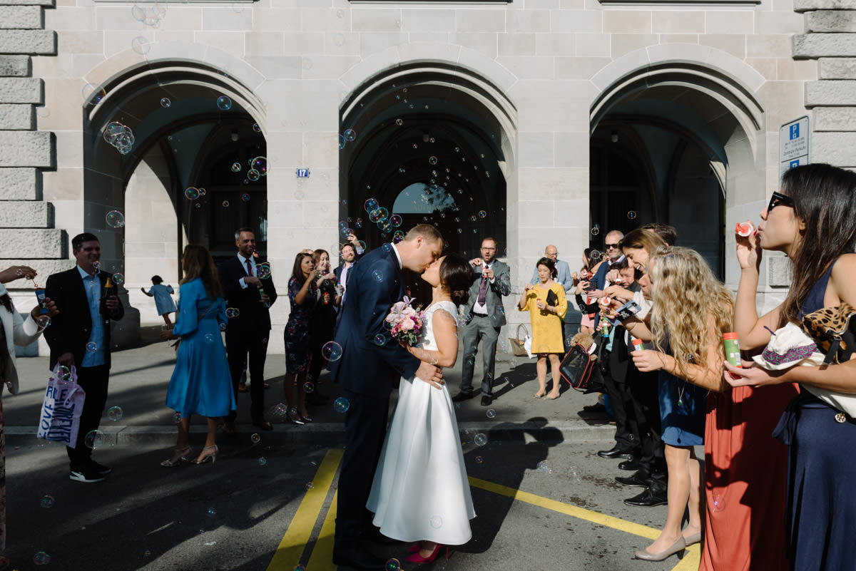 couple kissing with guests blowing bubbles outside the Stadthaus in Zurich on their micro wedding