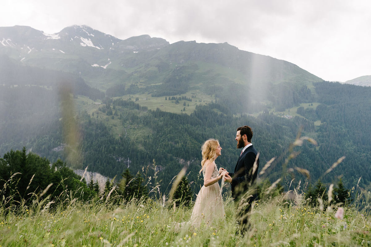 couple standing in a mountain meadow in Wengen Swiss elopement, they are loking at each other, she is in a pink dress