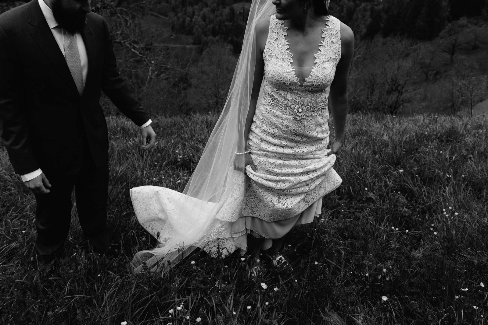 lazaro bridal dress armani suit standing in a meadow Switzerland