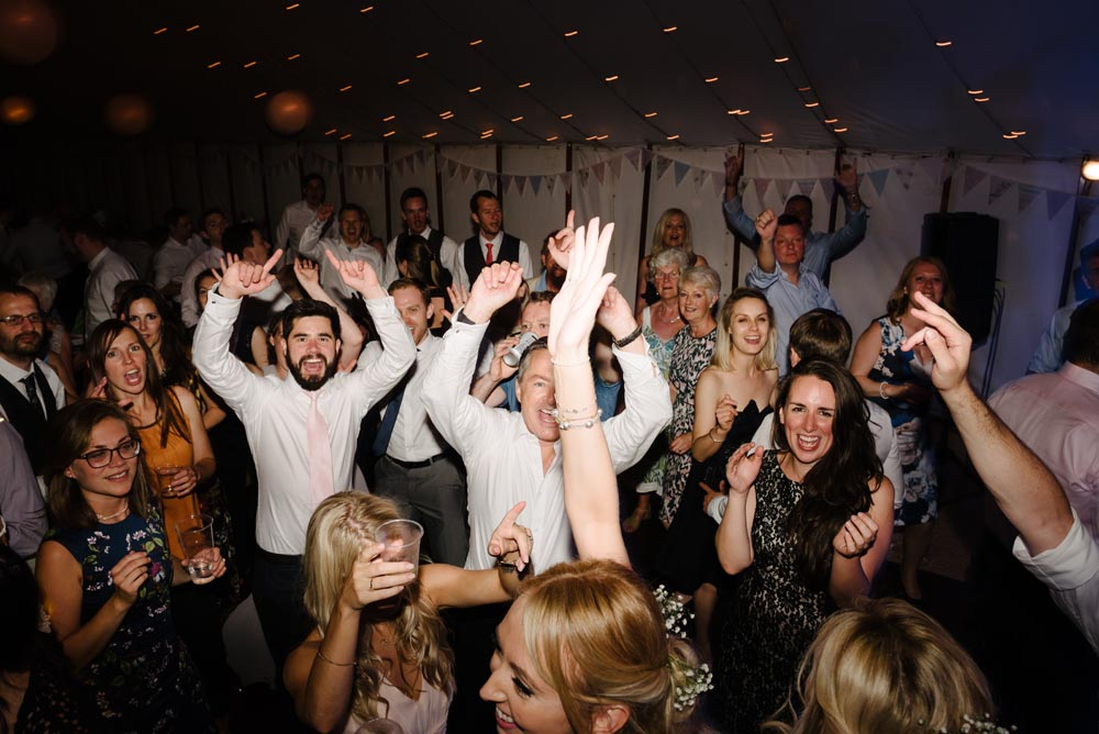 wedding reception in full swing people with hands in the air and singing
