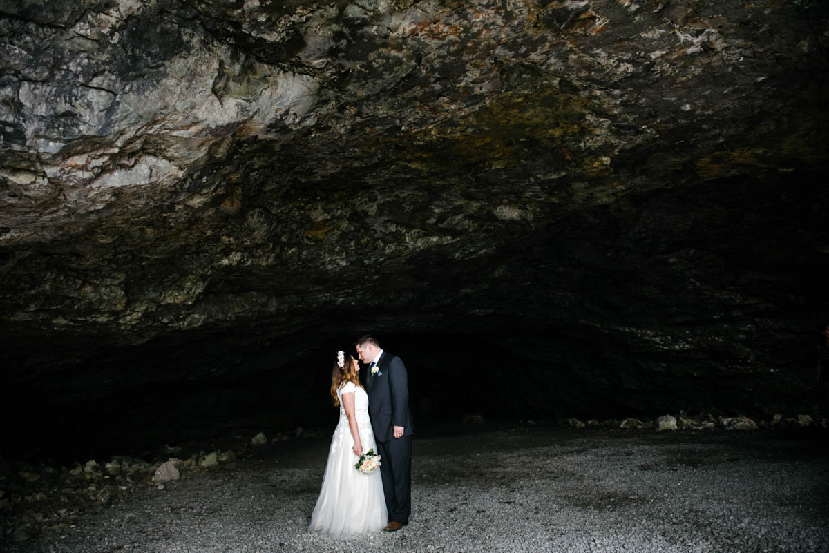 bride and groom on their elopement at the edge of a cave in the Swiss alps