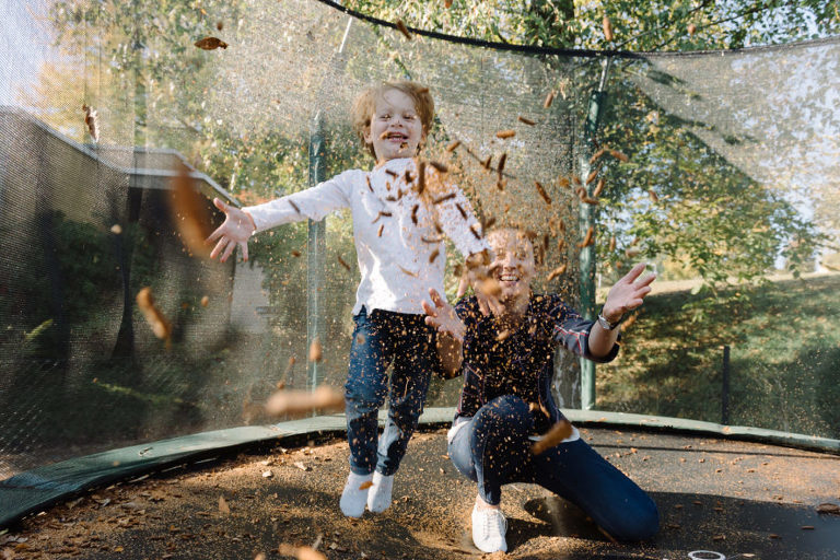 mum and son throwing autumn leaves on a trampoline family photo shoot in Switzerland
