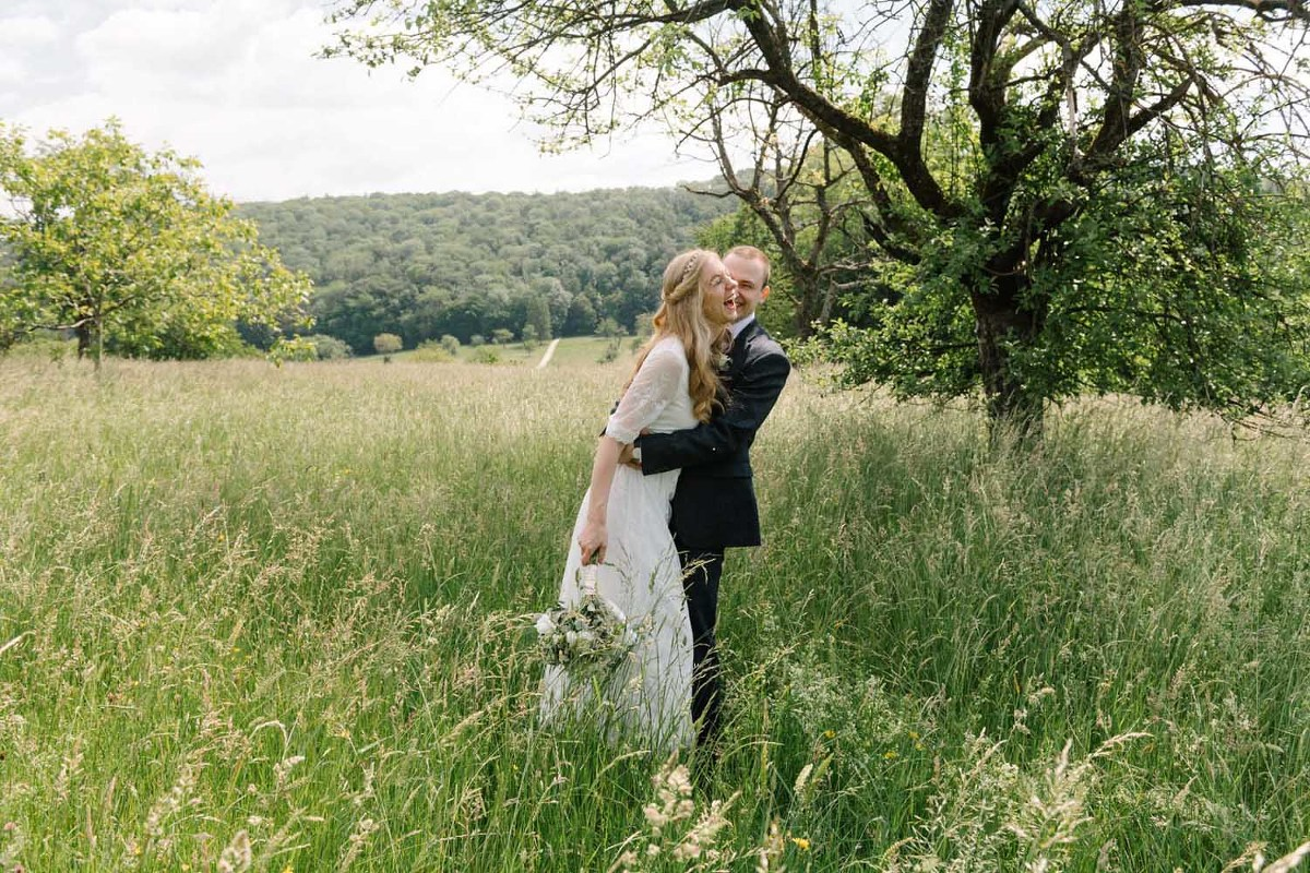 happy bride and groom in a field in Switzerland he is hugger her and she is laughing
