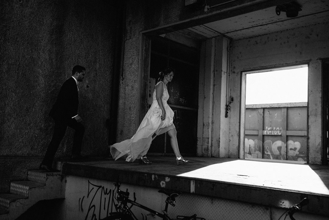couple walking wearing wedding clothes in an industrial wedding venue in Basel