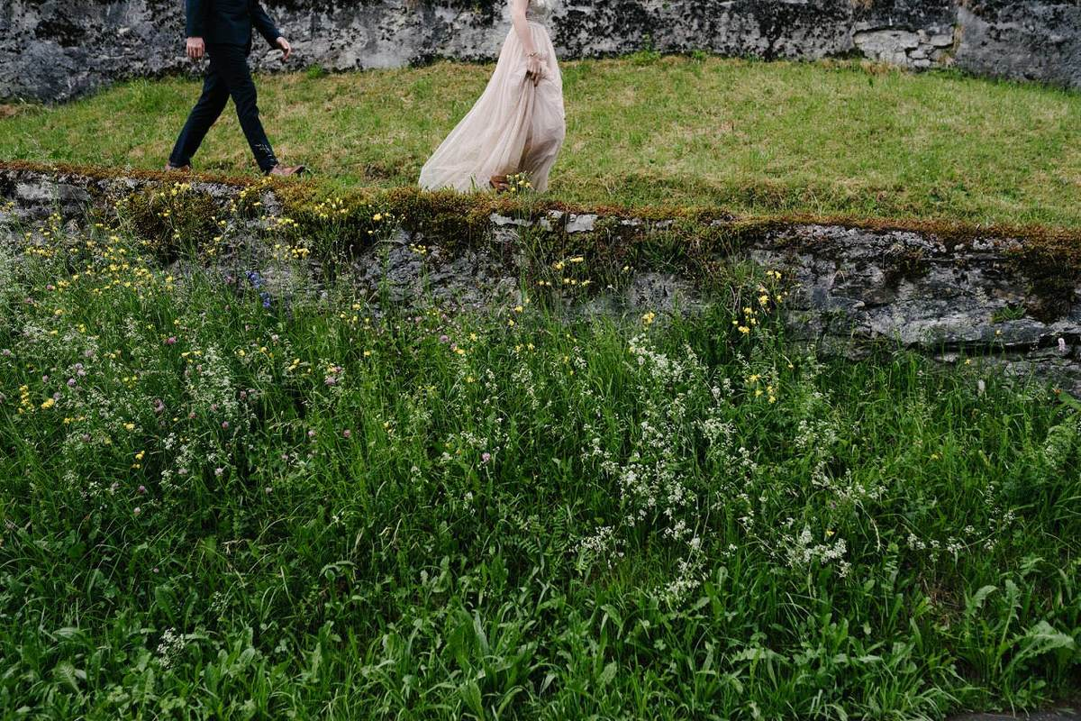 bride wears a pink dress groom is in a black suit they are walking down a path in a mountain village in the Swiss Alps