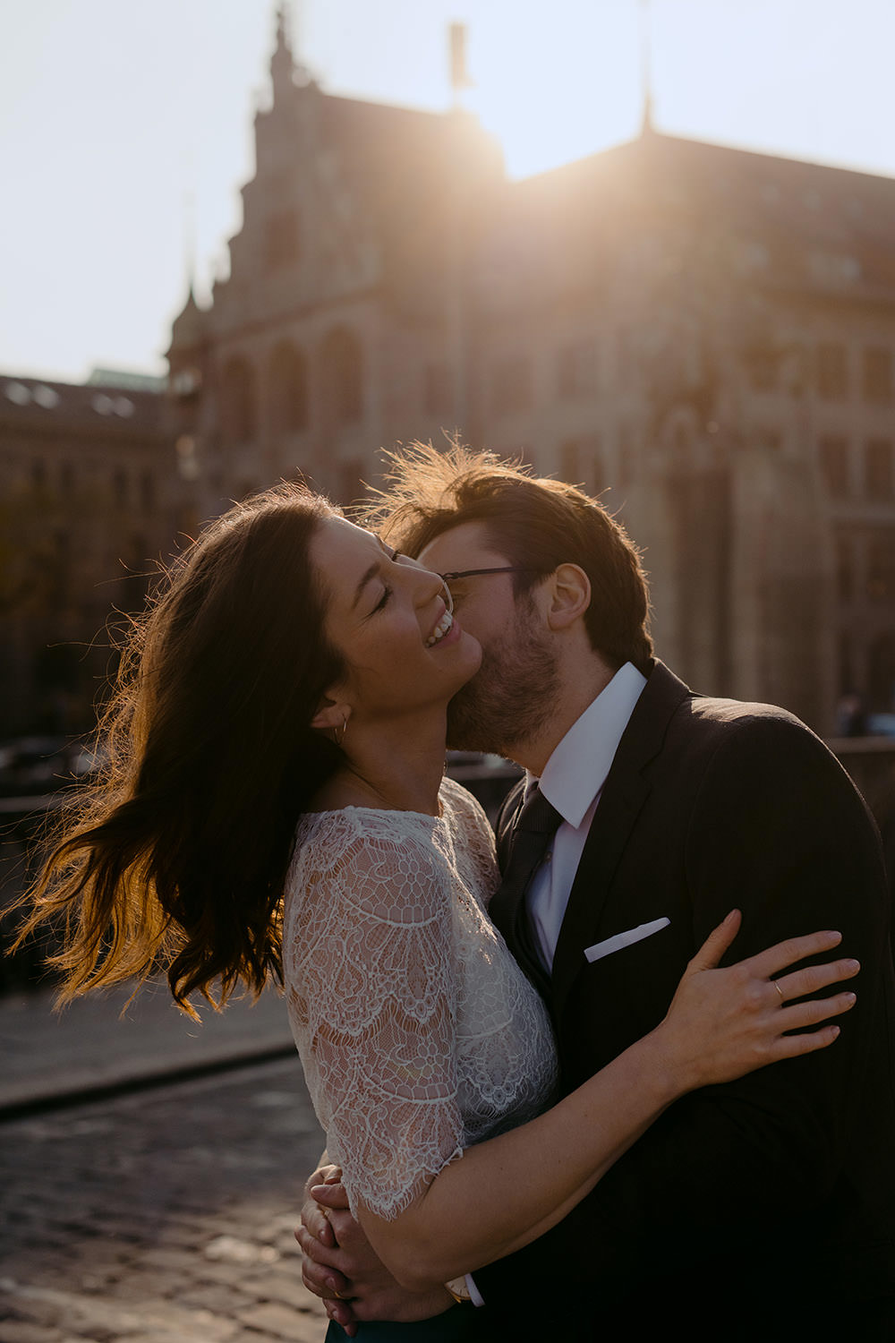 couple kissing in front of the Stadthaus in Zurich, her hair is blowing in the wind and she's laughting, he is kissing her neck